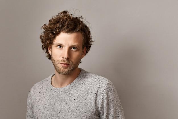 男性的な美しさ、スタイル、ファッションのコンセプト。スタイリッシュなニットのセーターを着て、コピースペースの壁に対して隔離されたポーズをとる無精ひげと青い目をしたファッショナブルな25歳の流行に敏感な男