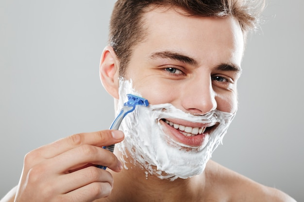 Masculine brunette guy with dark short hair shaving his face with razor and gel or cream being satisfied over grey wall close up