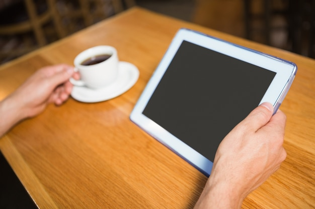 Masculine hands holding tablet and coffee