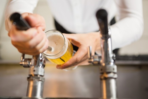Masculine hands pouring a pint