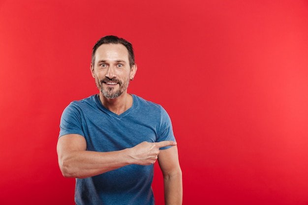 Masculine man 30s with european appearance in casual blue t-shirt pointing finger aside on copyspace, isolated over red background