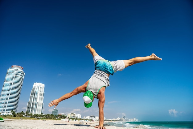 Masculine man standing on his hand with miami beach on background.