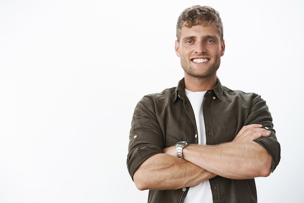 Masculine and strong good-looking man with white perfect smile and blue eyes cross hands against body in confident and assertive pose, satisfied and assured everything great over gray wall