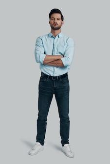 男らしさ。カメラを見て、灰色の背景に立っている間腕を組んでいるハンサムな若い男の全長