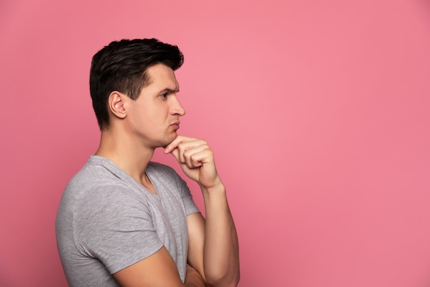 남성 다움. 왼손으로 턱을 만지면 서 프로필에 서서 무언가를 생각하는 회색 티셔츠의 잘 생긴 남자.