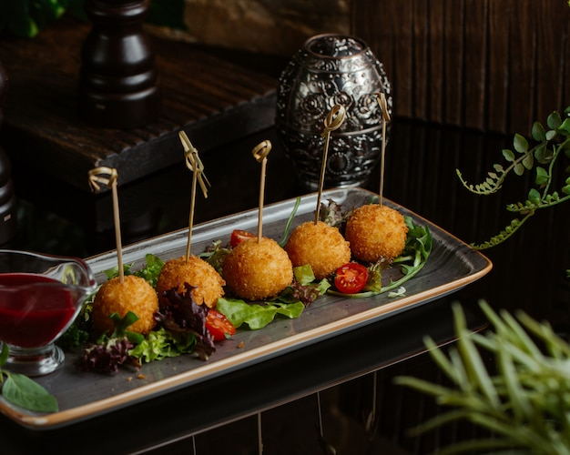 Mashed potato and cheese balls roasted and served with green salad inside a square granite plate