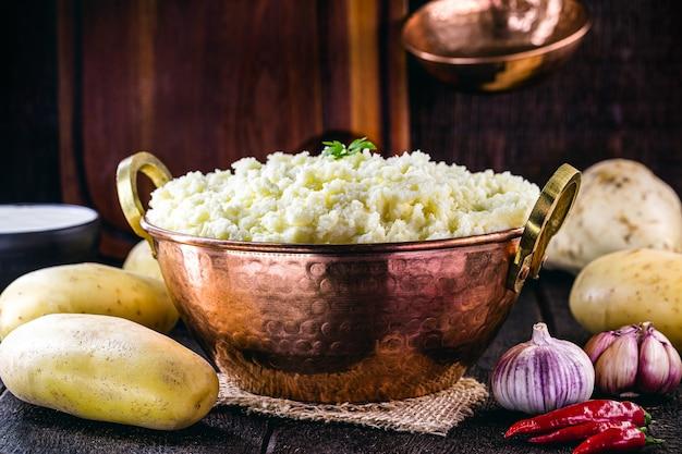 Картофельное пюре, картофельный крем на деревенской кухне, в деревенском медном горшочке