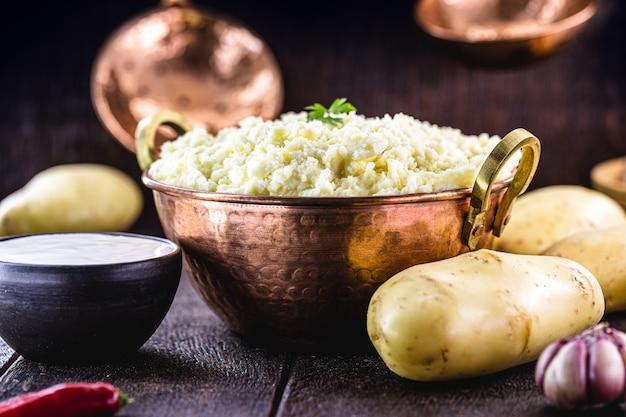 Mashed potato, potato cream in rustic kitchen, in rustic copper pot