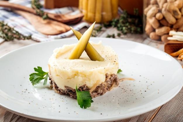 Картофельное пюре с говядиной в сливочном соусе и солеными огурцами