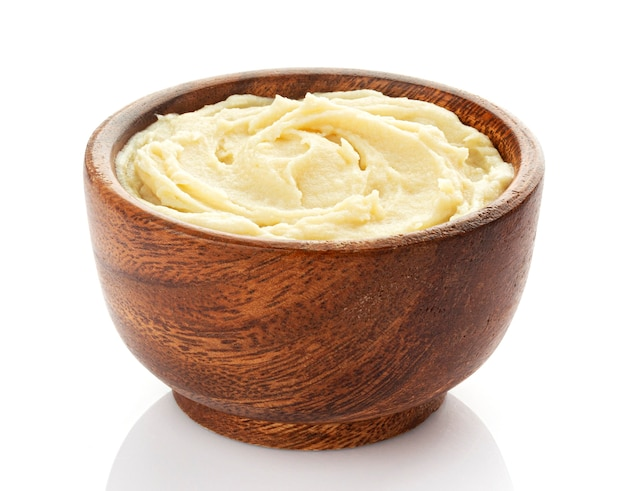 Mashed potato in wooden bowl isolated on white table, vegetable puree