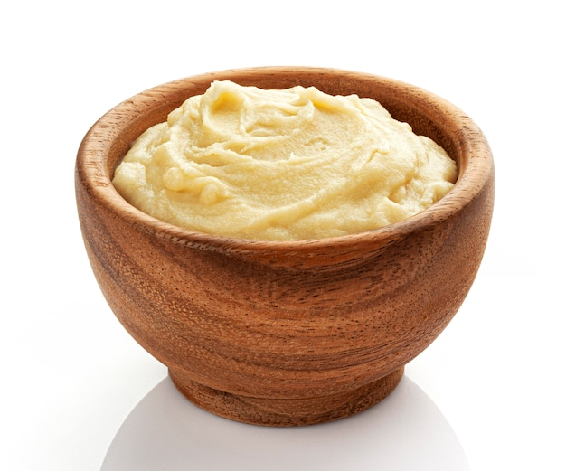 Mashed potato in wooden bowl isolated on white, vegetable puree