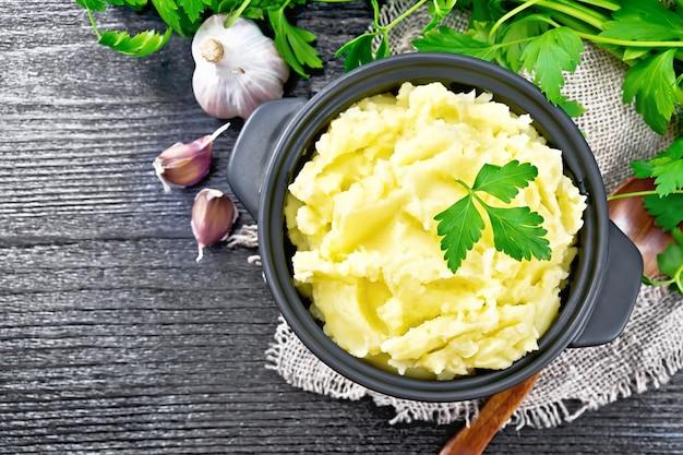 Картофельное пюре в черной кастрюле и ложка на мешковине, чеснок, петрушка на фоне деревянной доски сверху
