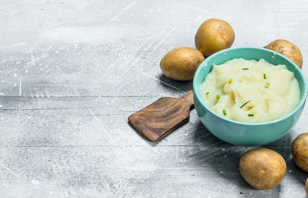 Картофельное пюре в миске на деревенском столе.