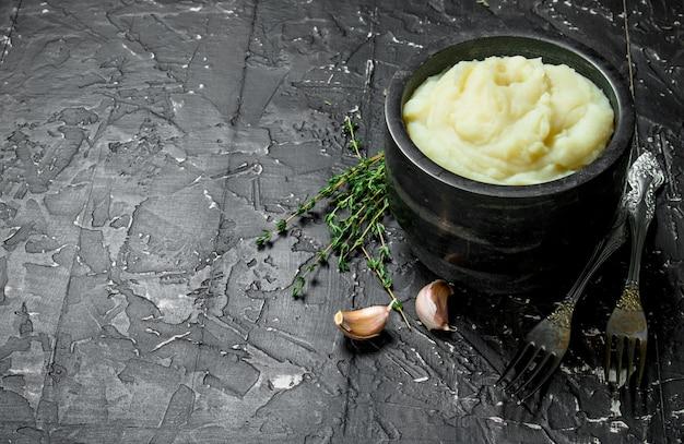 Картофельное пюре в миске с чесноком и тимьяном на черном деревенском столе.