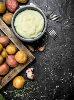 Картофельное пюре в миске с чесноком и тимьяном на черном деревянном столе