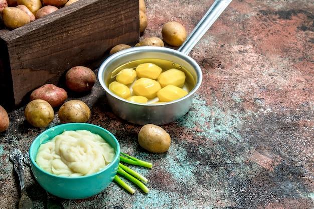 Картофельное пюре в миске с зеленым луком на деревенском столе.