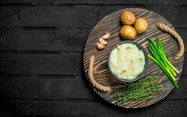 Картофельное пюре в миске с зеленью и чесноком на деревенском столе.