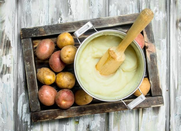 Картофельное пюре в горшочке на деревенском столе.