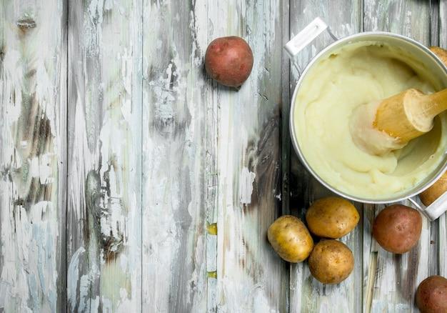 Картофельное пюре в горшочке на деревянном столе