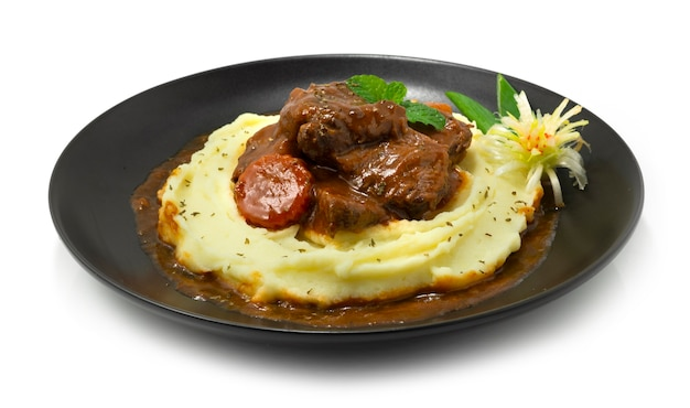 Картофельное пюре сверху с тушеной говядиной в соусе из красного вина вкусное основное блюдо европейская кухня украшение в стиле резные овощи, вид сбоку