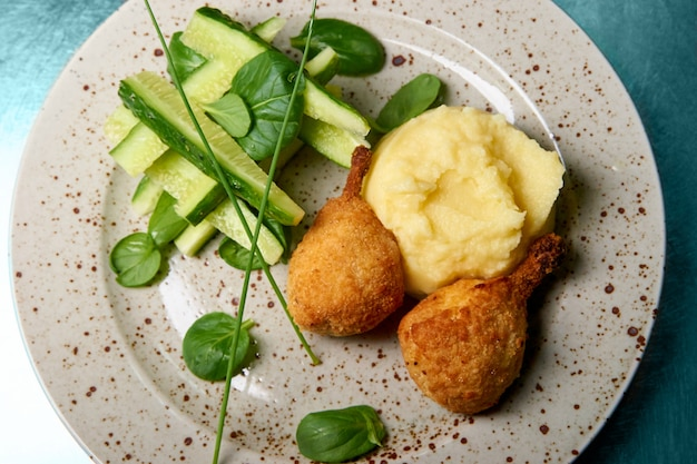 Mashed potatoes with crispy chicken and cucumbers.