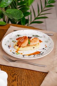 Картофельное пюре с котлетой, на красивой белой тарелке.
