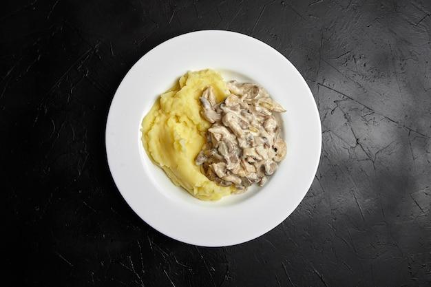 Картофельное пюре с жареными вешенками в белой керамической тарелке на черном каменном столе, вид сверху
