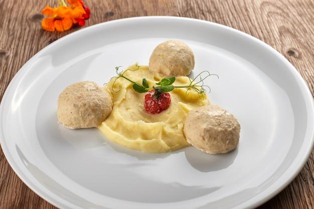Картофельное пюре с парными фрикадельками на белой тарелке