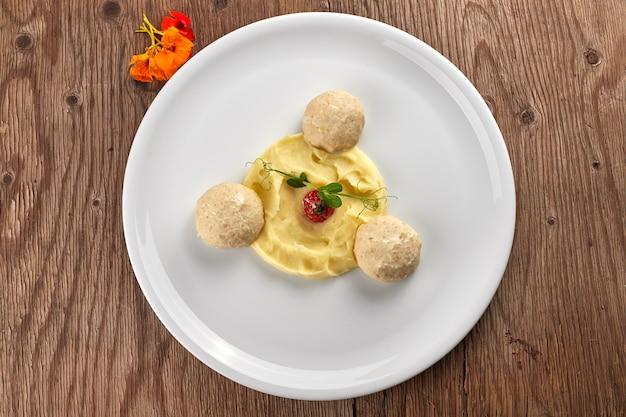 Картофельное пюре с паровыми тефтелями на белой тарелке