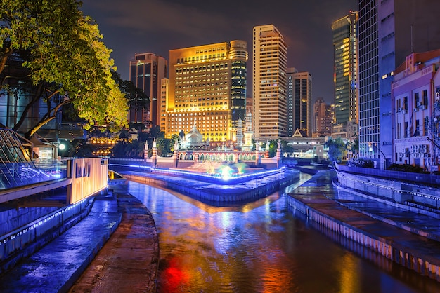 Masjid jamek and the blue pool in the heart of city center kuala lumpur at night in malaysia.
