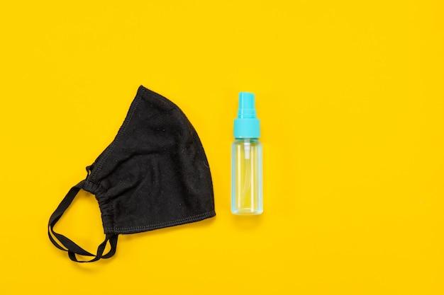 노란색 배경에 코로나바이러스의 확산을 방지하기 위한 마스크와 손 소독제