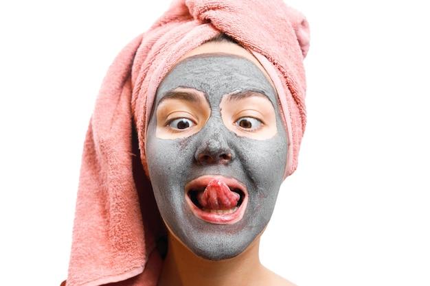피부를위한 마스크 여성, 소녀는 혀를 내고, 소녀는 맛에 얼굴 마스크를 시도합니다.