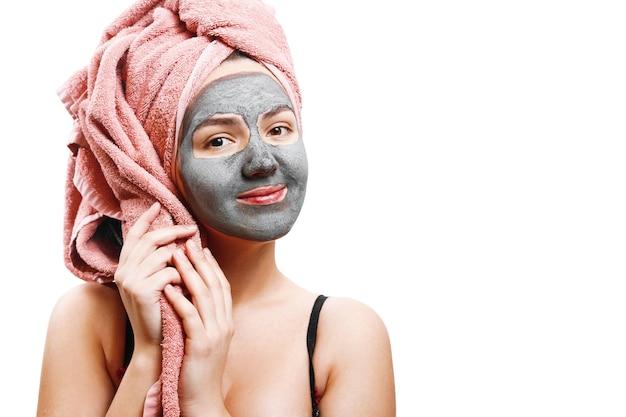 肌の女性のためのマスク、タオルを持っている幸せな女の子、女の子は顔の肌のためのマスクを楽しんでいます、孤立した写真、