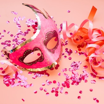 Mask near ribbons and set of rose confetti
