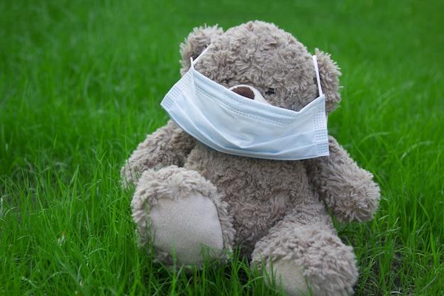裏庭の芝生の上のおもちゃのクマのマスク