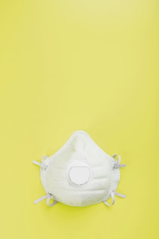 A mask to protect your breath from air pollution or an outbreak of flu or virus on a yellow surface