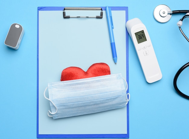 Mask and pulse oximeter, electronic thermometer and other medical supplies on blue, top view