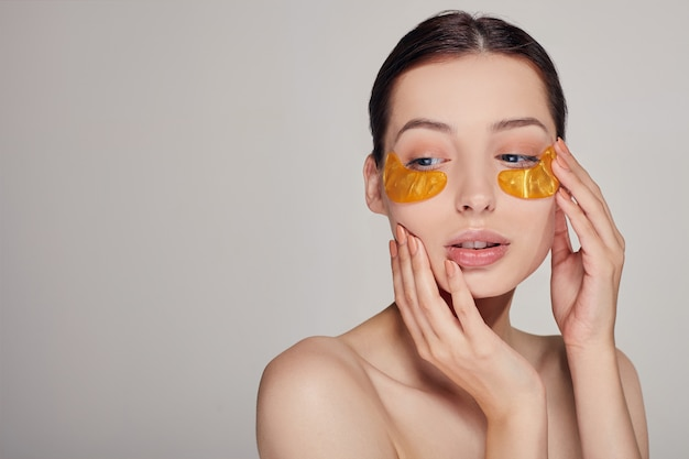 Mask for removing wrinkles and dark circles. a woman takes care of delicate skin around her eyes. cosmetic procedures.