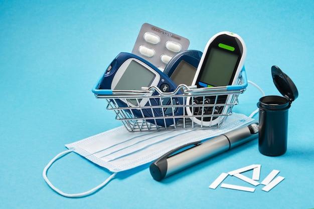 マスク、青い背景の買い物かごの中のいくつかの異なる血糖値計、ピル、テストストリップ、糖尿病患者用のインスリン注射器ペン、薬局のコンセプト