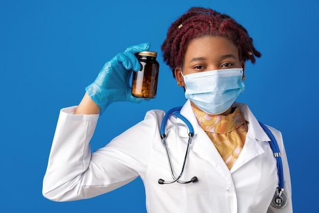 Афро-американская женщина-врач в маске показывает стеклянную банку с лекарством на синем фоне