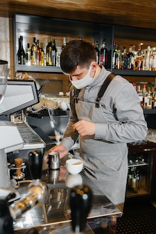 A masked barista prepares delicious coffee at the bar in a cafe. the work of restaurants and cafes during the pandemic.