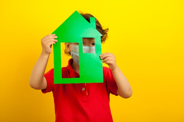 A masked boy holds in his hands a green house model and hides behind him only in the window.