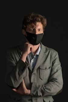 Деловой человек в маске смотрит серьезно, подперев кулак подбородком.