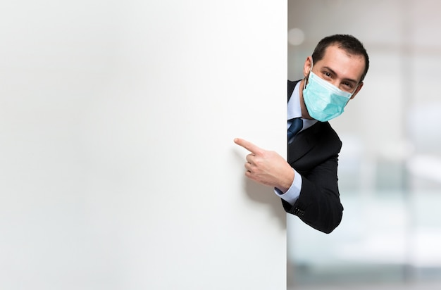空白のサインまたはパネルを示すマスクされたビジネスマン