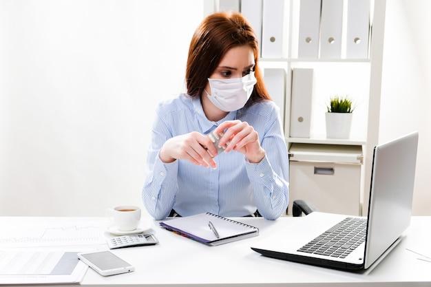 Бизнесмен в маске держит таблетки на рабочем месте
