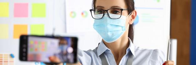 オフィスで仮面の実業家がスマートフォンでプレゼンテーションを記録しています。コロノウイルスの安全な職場のコンセプト