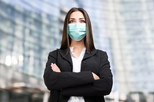 彼女のオフィス、コロナウイルスのパンデミックと仕事の概念の前に仮面の実業家