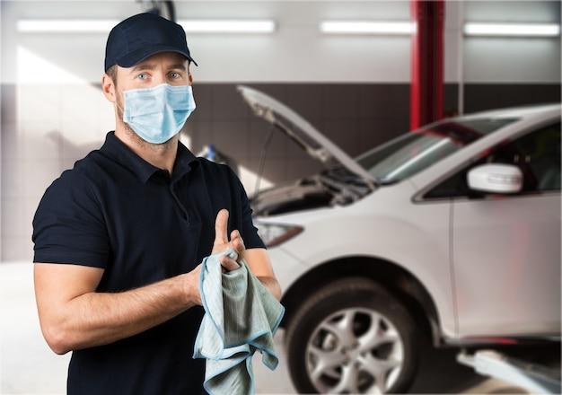 コロナウイルスのパンデミック中に働くマスクされた自動車整備士