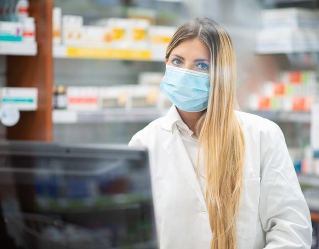 약국에서 가면을 쓴 점원, 코로나 바이러스 약사 개념