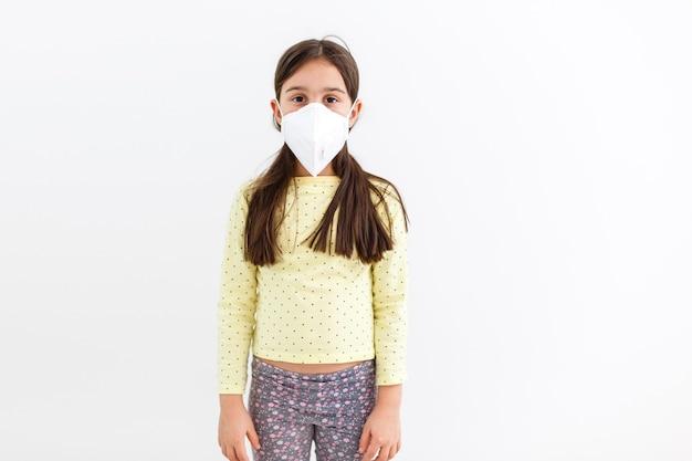 仮面の子供-インフルエンザウイルスに対する保護。 pm2.5を保護するためのマスクを身に着けている小さな白人の女の子。生物兵器。コピースペースと灰色の背景に赤ちゃん。エピデミックパンデミック。